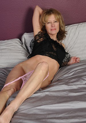 Slender mature lady taking off her lingerie and toying her trimmed pussy