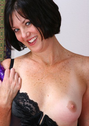 Smiley mature brunette pleasing herself with a ribbed sex toy on the bed