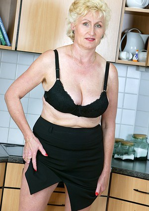 Lewd mature blonde uncovering her big saggy tits and hairy gash in the kitchen