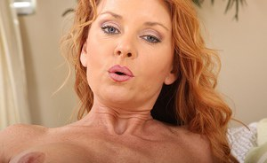Well-toned redhead MILF with round jugs toying her trimmed pussy on the bed
