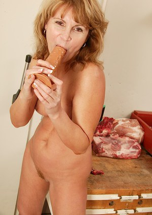 Sex-hungry mature lady with hairy cunt playing with a big realistic dildo