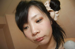 Smiley asian teen with hard nipples taking shower and caressing herself