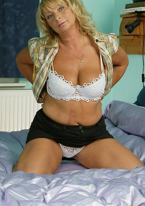 Dirty-minded mature blonde undressing and spreading her legs on the bed