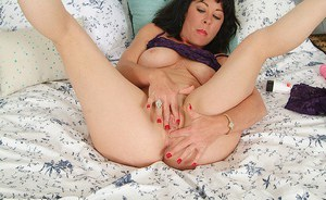 Sassy brunette lady revealing her goods and fingering her hungry cunt