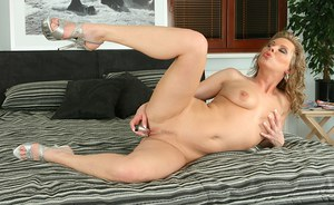 Nude MILF with nice tits and trimmed pussy playing with a metal vibrator
