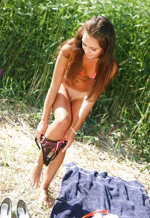 Horny teen sweetie undressing and teasing her pussy with her fingers outdoor