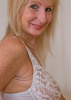 Lusty mature blonde with saggy tits undressing and fingering her twat