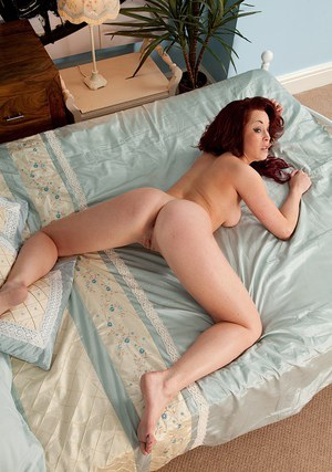 Ravishing redhead amateur with pierced belly-button posing nude on the bed
