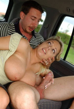 Slutty MILF with huge jugs goes down on a stiff cock on the back seat