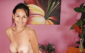 Smiley mature brunette lady revealing her tempting round boobies