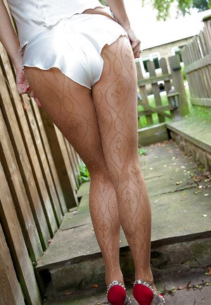 Sassy mature blonde in pantyhose revealing her jugs and shaved pussy outdoor