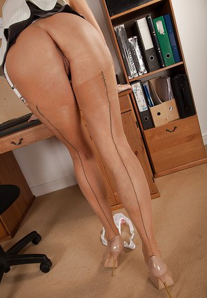 Liberated mature blonde in stockings uncovering her goods at her workplace