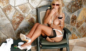 Voluptuous leggy MILF in sunglasses and stockings smoking cigarette