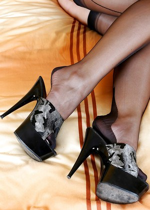 Lusty MILF takes off her high heels and exposes her nylon clad legs and feet