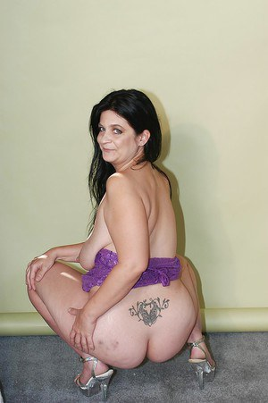 Fatty brunette MILF in gown revealing her jugs and ample ass