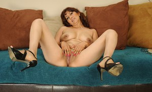 Mature vixen gets nude to expose her shaved cooter and sexy feet