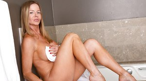 Well-toned blonde MILF with big jugs rubbing her slit in the bathroom