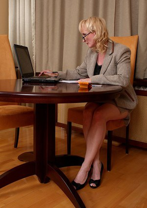 Sassy mature gal in glasses slowly uncovering her curvy body in her office