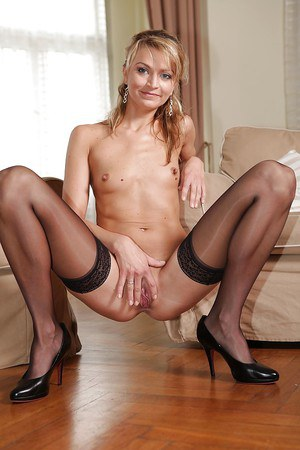 Slim blonde MILF stripping down and spreading her nylon clad legs