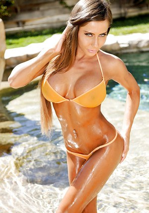 Ravishing babe with tanned skin revealing her big boobs at the poolside