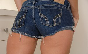 Smiley teen in jeans shorts stripping and exposing her slit in close up