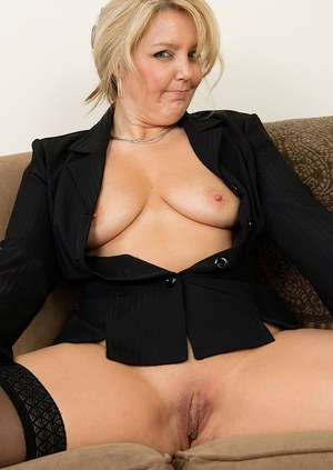 Sassy mature lady in glasses and nylons reveals her tits and shaved gash