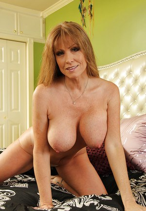 Busty mature vixen with shaved cunt undressing and spreading her legs