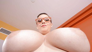 Playful sweetie in glasses revealing her huge melons and pink pussy