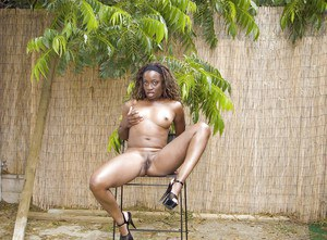 Salacious ebony chick in high heels undressing and spreading her legs