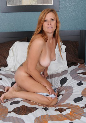 Smiley mature vixen in maid uniform undressing and exposing her gash