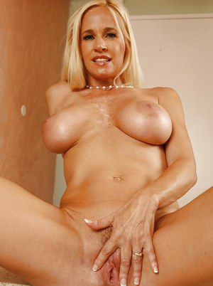 Full-bosomed blonde mature vixen undressing and spreading her legs