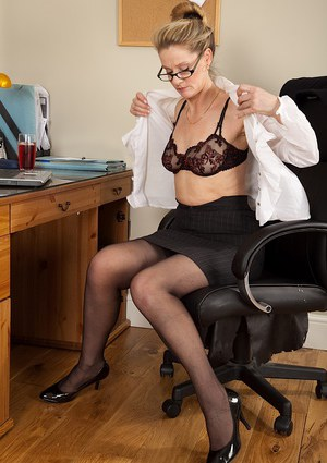Mature office vixen in nylons and glasses undressing and posing on her desk