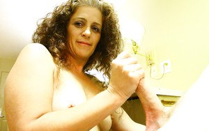 Curly-haired mature brunette gives a proper handjob on a stiff dick