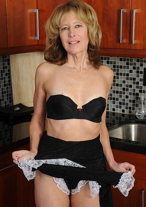 Naughty mature maid undressing and spreading her legs in the kitchen