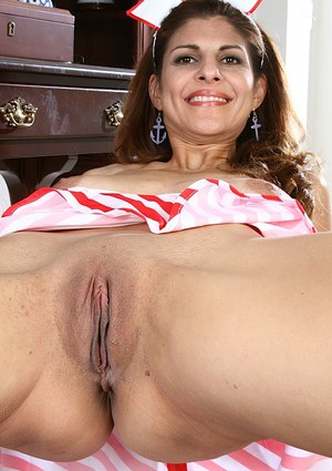 Mature lady with big tits takes off her nurse uniform to show pussy
