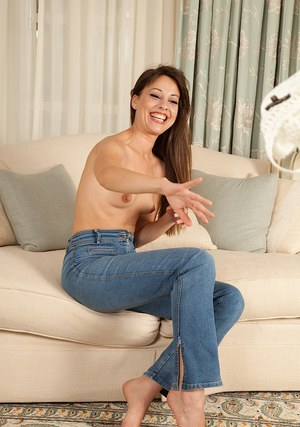 Admirable brunette in blue jeans undressing and posing on the couch