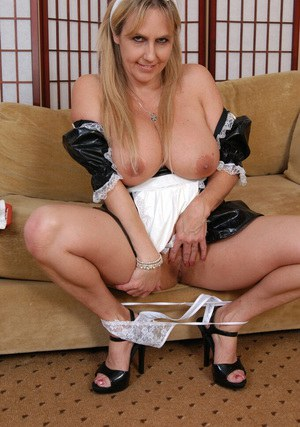 Top-heavy MILF in sexy maid uniform playing with a big black dildo