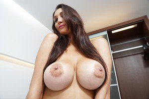 Top-heavy latina bombshell undressing and exposing her goods on the bed