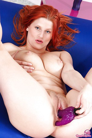 Redhead chick with massive melons pleasing herself with a vibrator