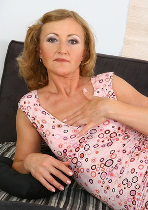 Sassy mature lady in glasses revealing her tits and pussy on the bed