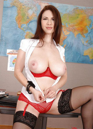 Top-heavy teacher in stockings and glasses getting nude in her office