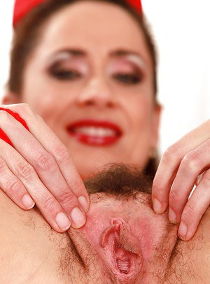 Lusty nurse in sexy uniform undressing and exposing her hairy gash