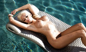 Graceful blonde centerfold with round boobies posing at the poolside