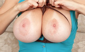 Sassy MILF with huge jugs undressing and playing with a big toy