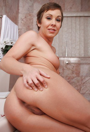 Short-haired MILF with tattoos showcasing her anal hole in the bathroom