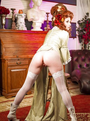 Glamorous redhead lady in white stockings uncovering her tattooed body