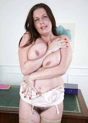 Salacious fatty mature gal in nylons exposing her big jugs and hairy twat