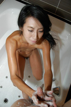 Skinny asian MILF gives a soapy handjob and wet nooky in the bathroom