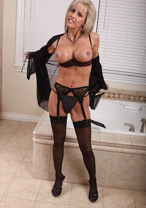 Smiley MILF stripping to her sexy lingerie and exposing her round jugs