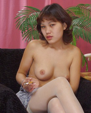 Nasty thhai girl in stockings smoking and revealing her bosoms
